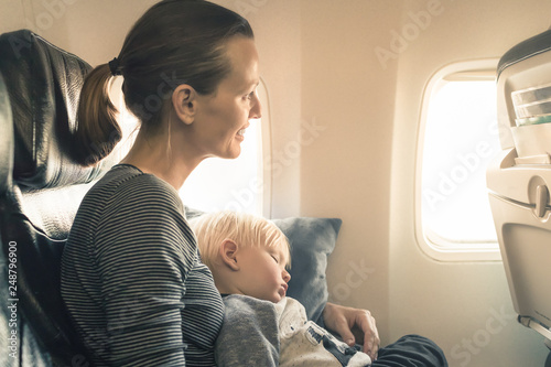 Happy mother traveling on airplane with her baby boy. Fototapet