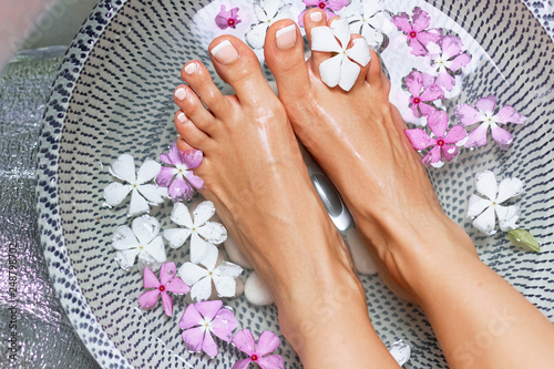 La pose en embrasure Spa Spa treatment and product for woman feet and foot spa. Foot bath in bowl with tropical flowers, Thailand. Healthy Concept. Closeup of beautiful female feet, legs at spa salon on pedicure procedure.