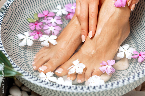 Foto auf Gartenposter Pediküre Spa treatment and product for female feet and foot spa. Foot bath in bowl with tropical flowers, Thailand. Healthy Concept. Beautiful female feet, legs at spa salon on pedicure procedure.