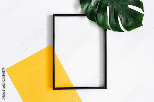 Obraz Summer composition. Tropical palm leaves, yellow paper blank, photo frame on pastel gray background. Summer concept. Flat lay, top view, copy space - fototapety do salonu