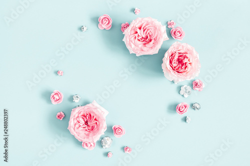 Flowers composition. Frame made of rose flowers on pastel blue background. Valentines day, mothers day, womens day, spring concept. Flat lay, top view, copy space