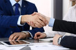 Business people shaking hands, finishing up a papers signing. Meeting, agreement and lawyer consulting concept