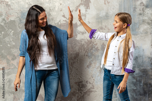 Valokuva  Portrait of an gladden mother and daughter giving high five over gray background