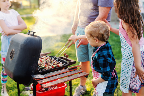 Fototapeta Little chef with apron grilling meat and vegetables on sticks. Next to him his cousins. Family gathering concept. obraz