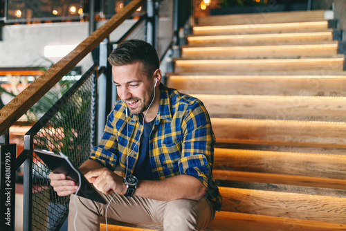 Photo  Smiling freelancer sitting on stairs indoors and using tablet for video call