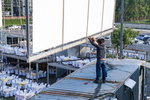 Two Worker Setup Outdoor Canvas Billboard On The Rooftop Of Container.