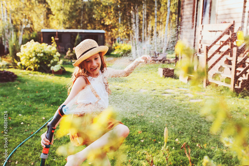 Fotografie, Obraz  happy child girl watering flowers with hose in summer garden, holding water spri