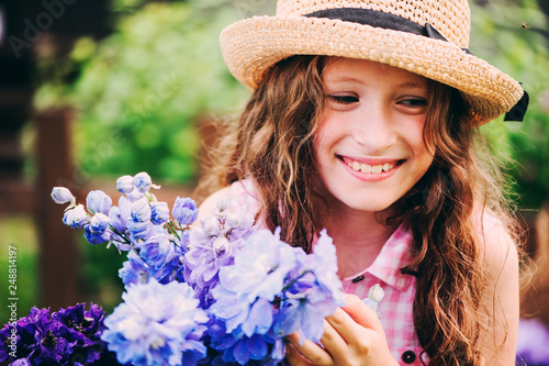 Fotografie, Tablou romantic portrait of happy child girl picking bouquet of beautiful blue delphini