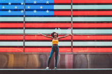 Woman With Arms Outstretched In Front Of American Flag On Times Square