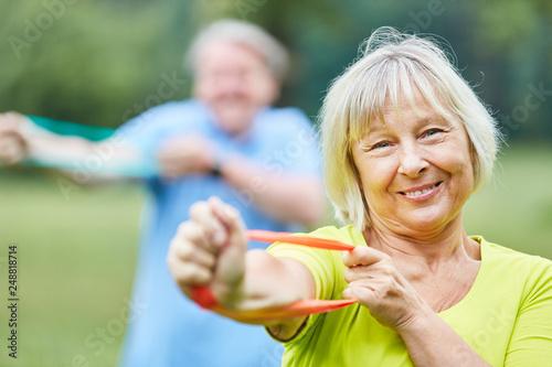 Fotobehang School de yoga Senior Frau trainiert mit einem Elastikband