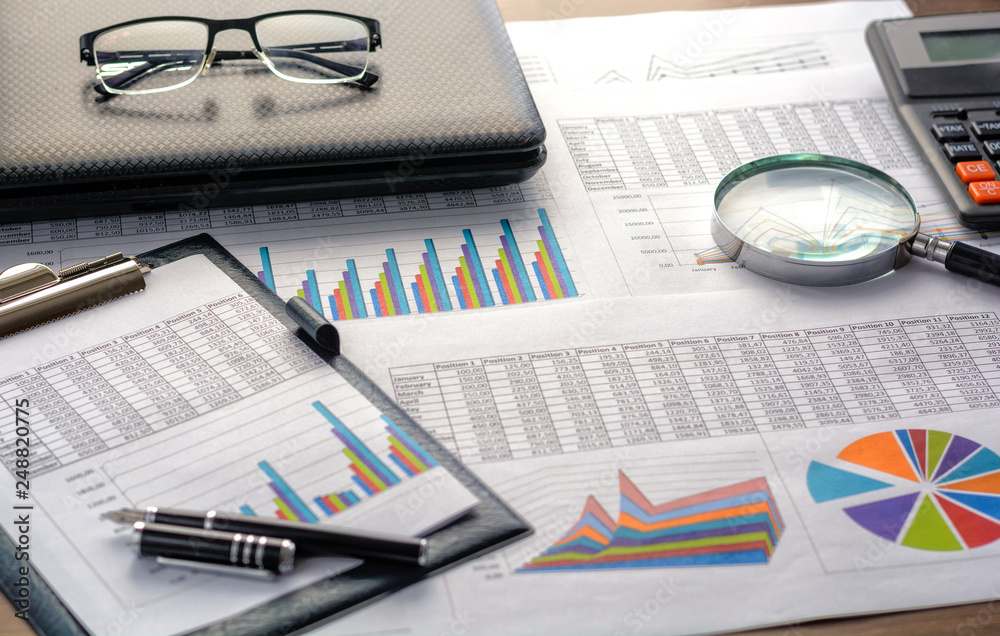 Fototapeta Financial documents - graphics, statistics, drawings, keyboard, laptop, magnifying glass in the office. Business, science, long hours of work.
