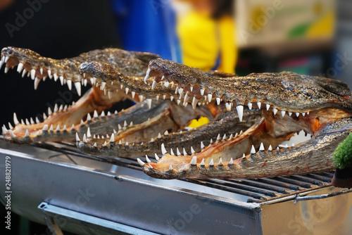 Poster Crocodile Roasted crocodile head on grill.
