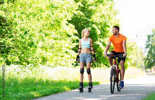 Fotografia fitness, sport and healthy lifestyle concept - happy couple with rollerblades an