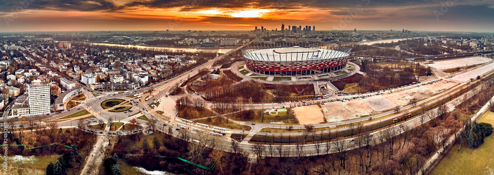 Fototapeta Beautiful panoramic aerial drone view to panorama of Warsaw modern City with skyscraper and The PGE Narodowy National Stadium (Polish: Stadion Narodowy) against the background of a dramatic sunset