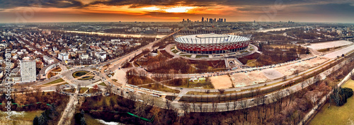 Fototapeta Beautiful panoramic aerial drone view to panorama of Warsaw modern City with skyscraper and The PGE Narodowy National Stadium (Polish: Stadion Narodowy) against the background of a dramatic sunset obraz