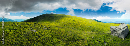 Foto auf AluDibond Rosa dunkel panorama with rock on the grassy hill in mountains. beautiful summer landscape. idyllic nature scenery. blue sky surrounded with clouds