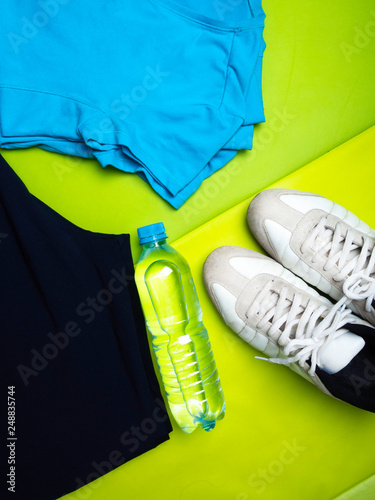 Fotografía  Sport clothing and accessories on green sport mat