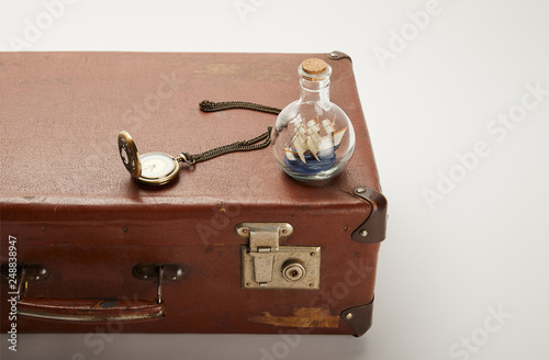 Fotografia  toy ship in glass bottle and compass on brown suitcase with copy space