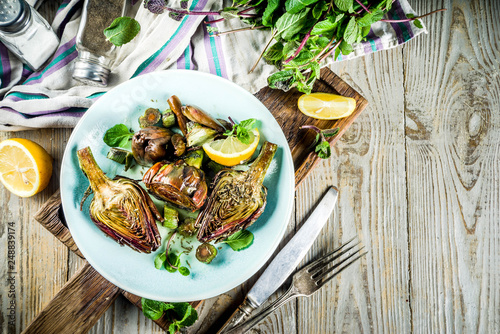 Photo Cooked baked artichoke, alla romana, grilled artichoke flowers with olive oil, lemon, garlic, mint  and spices