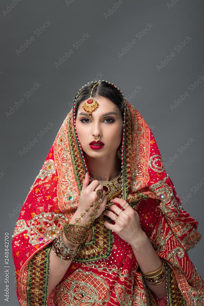 Fototapeta beautiful indian woman posing in traditional sari, isolated on grey