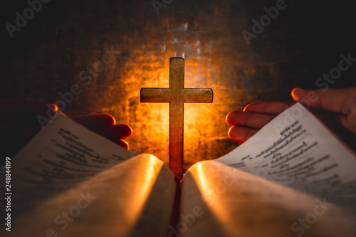 Obraz na plátně  opening bible with cross in middle at light of candle background on wooden table