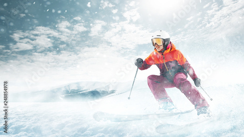 Papiers peints Glisse hiver Young beautiful athlete woman doing winter sport - she is skiing against white alps mountain background