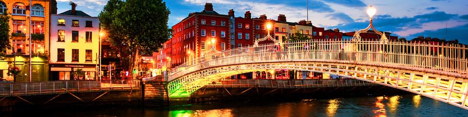 Night view of famous illuminated Ha Penny Bridge in Dublin, Ireland at sunset