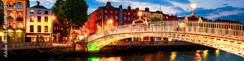 Photo Night view of famous illuminated Ha Penny Bridge in Dublin, Ireland at sunset