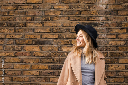 Portrait of beautiful smiling Caucasian woman standing by the brick wall wearing camel coat and a hat. - 248856514