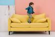 Leinwandbild Motiv cute little boy in blue jacket and green jeans jumping on yellow sofa