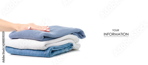 Fotografía  Stack of clothing jeans sweaters in hand pattern on a white background isolation