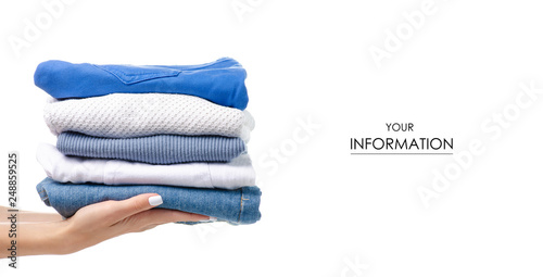 Obraz Stack of clothing jeans sweaters in hand pattern on a white background isolation - fototapety do salonu