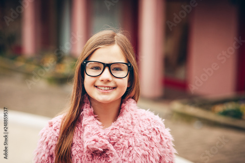 554cd04fc5 Outdoor portrait of cute young kid girl wearing eyeglasses and pink coat