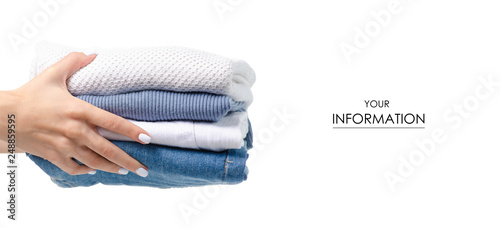 Photo Stack of clothing jeans sweaters in hand pattern on a white background isolation