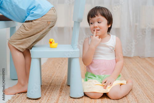Fotografie, Obraz  Sister puts a rubber duck on a chair under her brother's ass and hides on fool's day