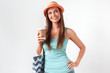 Thinking creative. Woman in hat standing studio isolated on white with beach bag holding cup of coffee smiling happy