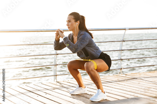 Fotografía  Concentrated sportswoman doing exercises with a rubber band