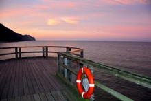Wooden Pier With One  Red Lifebuoy On The Baltic Sea After Sunset, Overlooking The Sea With Copy Space