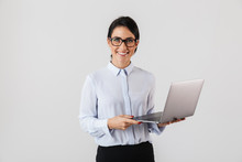 Portrait Of Young Businesswoman Wearing Eyeglasses Holding Silver Laptop In The Office, Isolated Over White Background