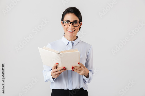 Fotografía  Photo of smiling female worker wearing eyeglasses reading book in the office, is