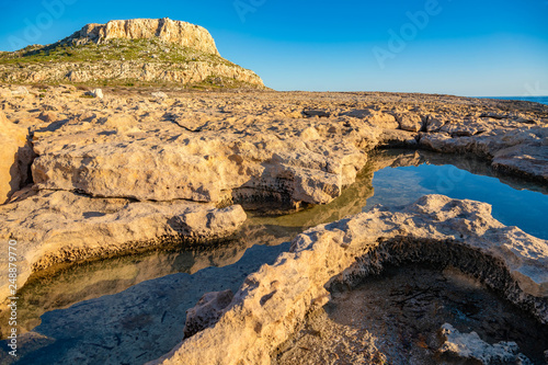 Beautiful landscape with reflection of rocks in the water. Ayia Napa coastline at sunset. Cape Greco National Forest Park, Cyprus.
