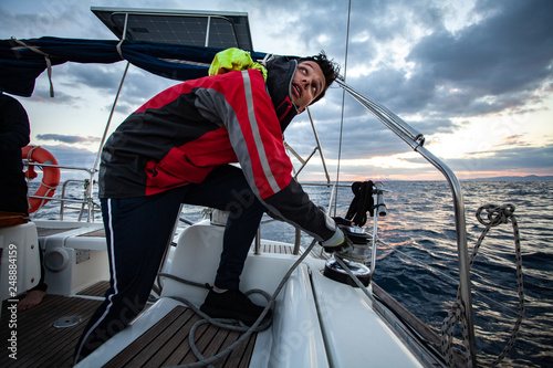 Fotomural Young sailor guy sets sail on a boat.