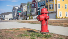 Close Up Bokeh Shot Of A Bright Red Fire Hydrant With Brightly Colored Townhouses In The Background.