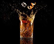 Orange Zest And Ice Falling Into Splashing Cocktail Isolated On Black