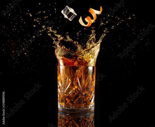 Photo orange zest and ice falling into splashing cocktail isolated on black