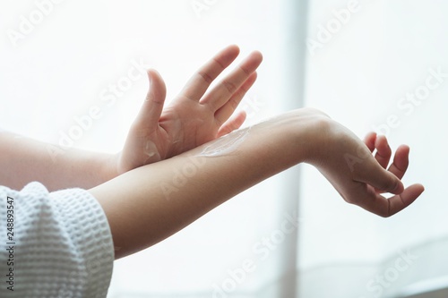 Fotografie, Obraz  Woman in bathrobe applying moisturizing hand cream, closeup