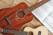 Music Education. Brown Acoustic Guitar And Ukulele Lying On The Wooden Floor With Music Notes. Top View