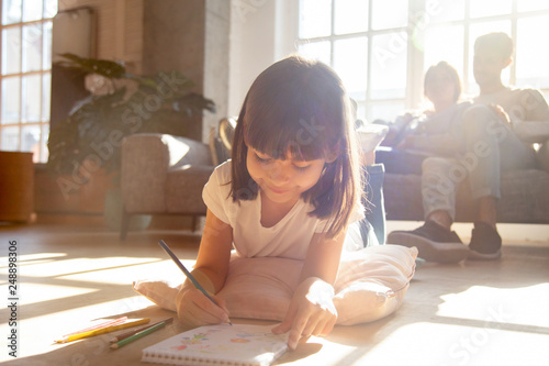 Obraz Cute kid girl drawing with colored pencils lying on floor - fototapety do salonu