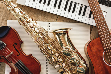 Power of music. Top view of musical instruments set: synthesizer, guitar, saxophone and violin lying on the sheets for music notes over wooden floor