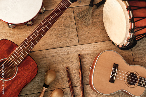 Ethnic musical instruments set: tambourine, wooden drum, brushes, wooden sticks, maracas and guitars laying on wooden floor. Top view - 248902366